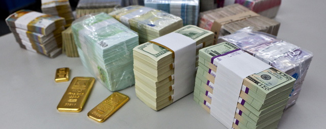 "Bundles of bank notes (US dollars, Euros, Swiss francs and British pounds) and gold bars at the bank vault of the ""Zuercher Kantonalbank"" bank, pictured on August 9, 2011 in Zurich, Switzerland. (KEYSTONE/Martin Ruetschi)"