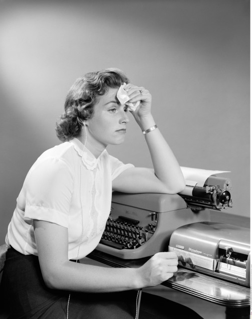1950s AILING WOMAN SECRETARY SITTING AT DESK WITH TYPEWRITER AND DICTATION MACHINE HOLDING HANDKERCHIEF TO FOREHEAD