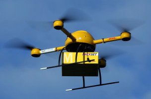 An unmanned aerial vehicle (UAV) carries a parcel in Bonn, Germany, 09 December 2013. Deutsche Post DHL has for the first time tested parcel deliveries with a drone. Photo by: Oliver Berg/picture-alliance/dpa/AP Images