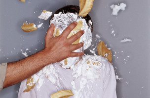 Teenage boy (14-16) having cream pie thrown at face