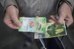 Ein Mann vergleicht die neue 50 Franken Note mit der Alten, aufgenommen am Dienstag, 12. April 2016 in Zuerich. (KEYSTONE/Ennio Leanza)