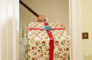 Senior man carrying large Christmas present through doorway