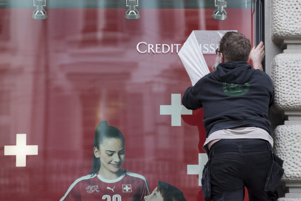 A man works on a new banner of the Swiss bank Credit Suisse in Zurich, Switzerland, Tuesday, May 10, 2016. Switzerland's second-biggest bank on Tuesday reported a net loss of 302 million Swiss francs ($311 million) in the three months through March, compared with a profit of 1.05 billion francs a year ago. (KEYSTONE/Ennio Leanza)