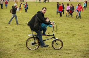 A man cycles with his son near the Little Big tent on the second day of Electric Picnic music festival at Stradbally Hall in County Laois