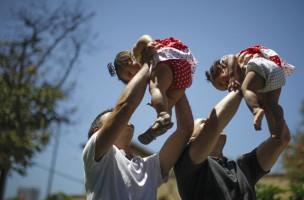 Hausmann im Doppel: Ehepaat Jason How und Adrian Perez mit ihren Zwillingstöchtern auf dem Spielplatz. (Reuters/Lucy Nicholson)