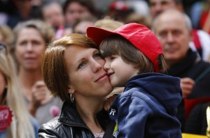 A nurse holds her son as she takes part in strike action in Frankfurt