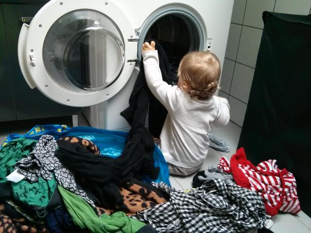 Kleinkind beim Sortieren der Wäsche