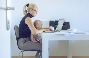 Attractive barefoot woman working on a laptop computer holding her baby in her arms. The woman is casually dressed with long blonde hair that is swept back from her face. She looks concentrated and she is probably doing her budget or paying bills. Also, she could be a business woman that works at home. The shot is executed with available natural light, and the copy space has been left. Shallow DOF; Soft focused; developed from RAW; retouched with special care and attention; small amount of grain added for best final impression; ready made for print and web use.