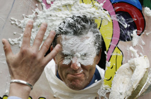 The Chairman of Pan American Silver Corporation Ross Beaty is hit in the face with a pie during fundraising for Sick Children's Hospital in Vancouver, British Columbia May 12, 2005. The pie throwing is part of the Mining for Charity Fair held annually in the city. REUTERS/Andy Clark  AC - RTRAYUX