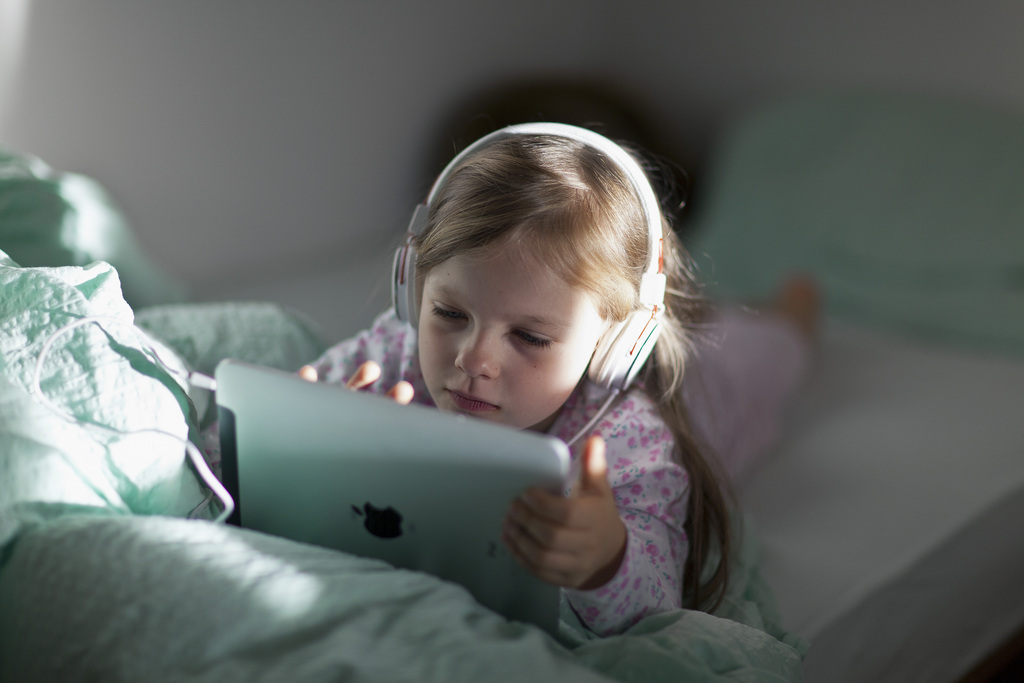 A seven-year-old girl is playing and listening to music using her ipad(1) in the hotel room. Pictured on October 10, 2012, in Zernez, Switzerland. (KEYSTONE/GAETAN BALLY)