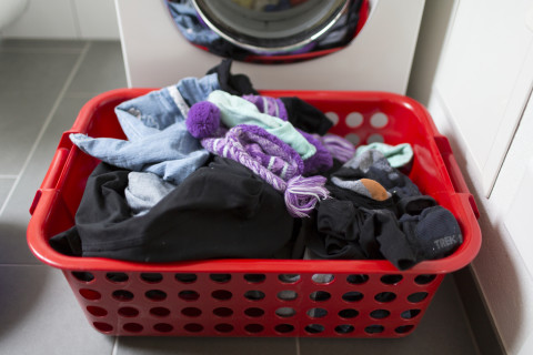 Washing machine with laundry basket on floor, pictured on June 2, 2013, in Switzerland. (KEYSTONE/Gaetan Bally)