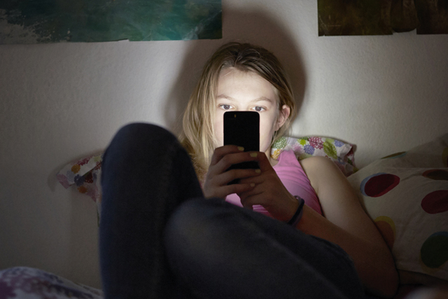 [ Symbolic Image, Posed Picture, Model Released ] - Girl sitting on her bed using mobile phone to surf on the internet, to chat. (Photo by KEYSTONE/Christof Schuerpf) [ Gestellte Aufnahme, Symbolbild, Model Released ] Kind, Maedchen, Telefon, Mobile Phone, Surfen, Chatten, Internet, Pornografie, (KEYSTONE/Christof Schuerpf)