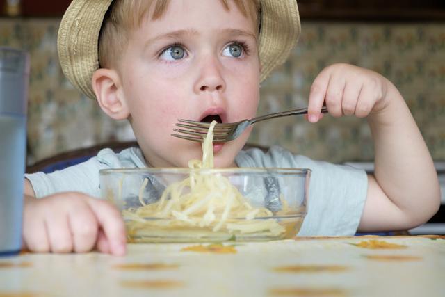 Portrait of little boy eating spaghetti