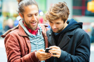 Young man sharing media with friend on mobile phone. Close-up version; they are both smiling.
