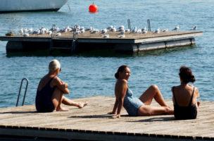 Waehrend ein Floss bereits von Moewen besiedelt wird tummeln sich am Sonntag, 21. September 2003, auf einem weiteren in der Badeanstalt Enge in Zuerich noch einige Badegaeste. Obwohl die Temperaturen tagsueber noch durchaus sommerlich sind, schliessen an diesem Wochenende weitere Badeanstalten.  (KEYSTONE/Steffen Schmidt)