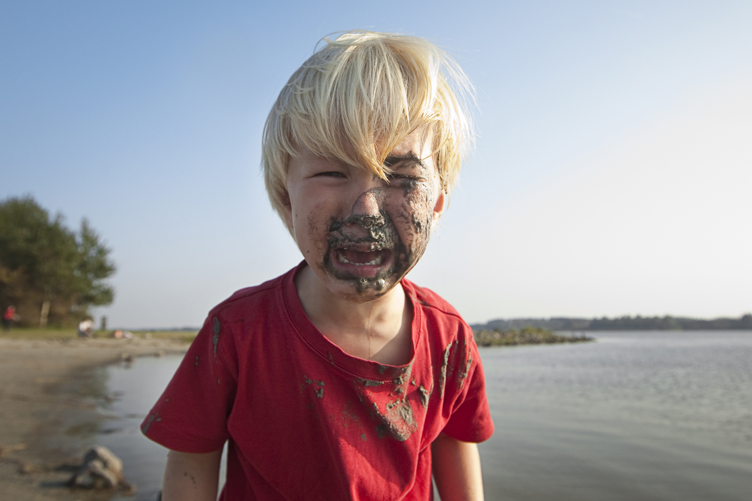pity,sad, boy, child, childhood, red, shirt, cry, mud, dirt, face, lake, water, sunny, blue sky, blond, fair, shout, moan, weep, groan, tears, tree, sand, beach, rocks, floodlight, outdoor, county life, crisis,