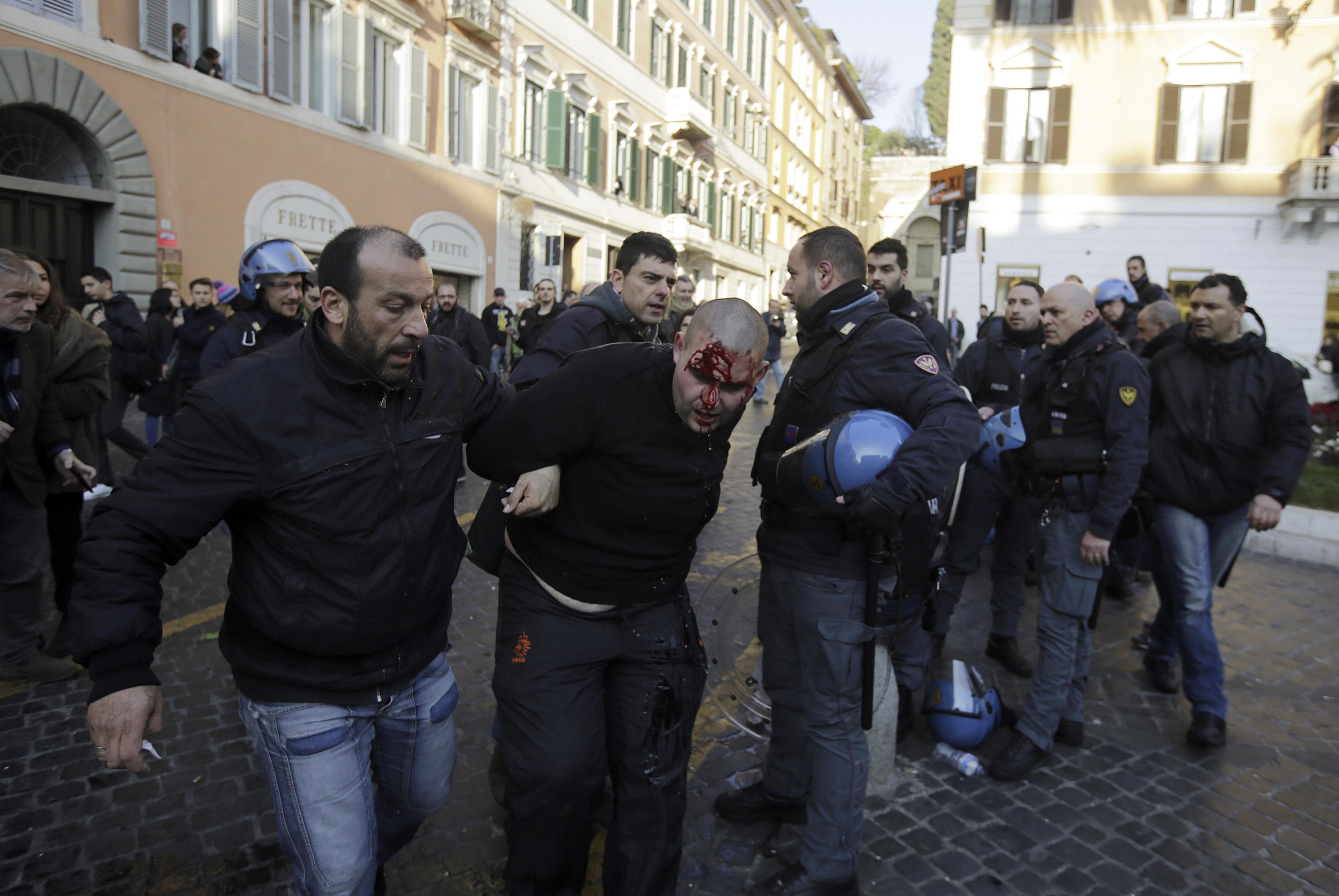 Ein blutender Feyenoord-Anhänger wird am Nachmittag vor dem Roma-Spiel in der Nähe der Spanischen Treppe in Rom abgeführt. Foto: Yara Nardi (Reuters)