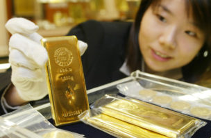 AN EMPLOYEE DISPLAYS A GOLD BAR AT A JEWELRY STORE IN TOKYO.