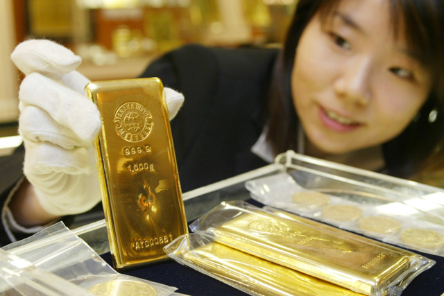 Der Goldstandard ist kein Garant für Stabilität: Eine Angestellte eines Juweiliergeschäfts in Japan mit einem Goldbarren. (Bild: Reuters)