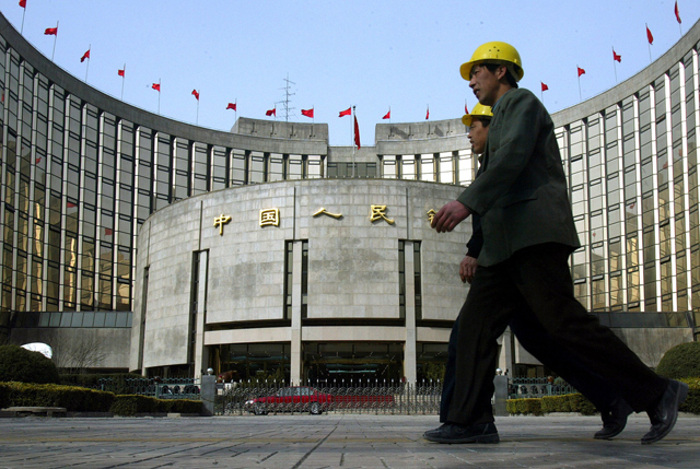 Chinese construction workers walk past the main office of the People's Bank of China in Beijing, China, Thursday, March 11, 2004. Zhou Xiaochuan, governor of the People's Bank of China, said the central bank will watch the country's lending more closely after a boom in landing last year led to a brief spurt of inflation at a press conference Thursday. (KEYSTONE/AP Photo/Ng Han Guan)