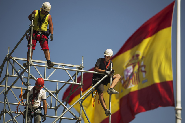 Workers build a structure in front of the Spanish flag in Madrid, Spain, Tuesday, Sept. 2, 2014. The number of people registered as unemployed in Spain grew by 8.070 in August, leaving the total number at 4.427.930 of people, Spain's Labor Ministry said. (AP Photo/Andres Kudacki)