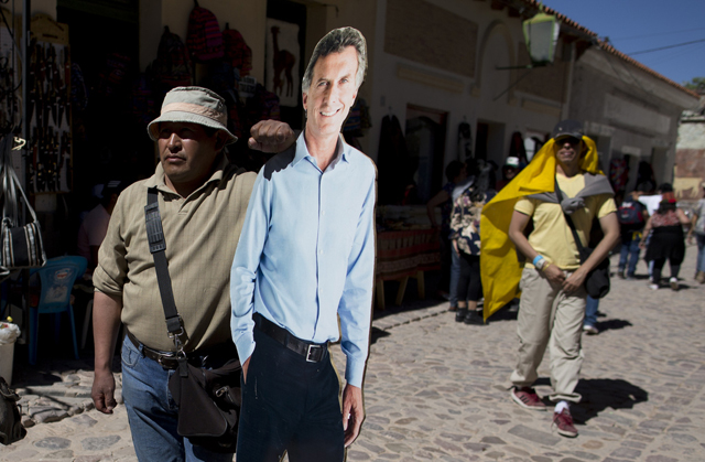 A supporter poses with a life-size cutout of opposition presidential candidate Mauricio Macri before the start of his closing campaign rally in Humahuaca, Jujuy, Argentina, Thursday, Nov. 19, 2015. Macri will face the ruling party candidate Daniel Scioli in a Nov. 22 runoff. The election comes at a time when Argentina's economy, the third largest in Latin America, has stalled. Inflation is around 30 percent, gross domestic product growth is just above zero and many private economists warn that the current administration's spending is not sustainable. (Keystone/Natacha Pisarenko)