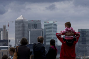 People look at a view of the Canary Wharf business district in London, which includes the headquarters building of HSBC, Tuesday, June 9, 2015.  HSBC Holdings, Europe's largest bank by market value, will cut up to 25,000 jobs globally to reduce costs and shift its center of gravity further toward the fast-growing Asian economies where it started operations 150 years ago.  (AP Photo/Matt Dunham)