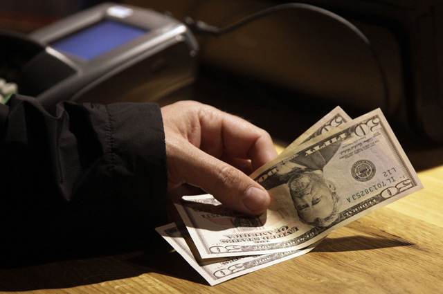 Cash is tendered at opening of the Superdry store in New York's Times Square, Wednesday, May 9, 2012. (AP Photo/Richard Drew)