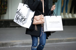 A customer carries shopping bags with purchases outside a department store in Paris, France, February 26, 2016. French consumer prices fell 0.1 percent over 12 months, the INSEE statistic agency said in a first estimate of EU-harmonised inflation data. Economists polled by Reuters had expected on average an inflation rate of 0.1 percent in February. REUTERS/Charles Platiau  - RTX28Q78