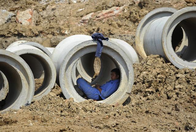 Inmitten riesiger Überkapazitäten: Ein Arbeiter schläft in einer Zement-Pipeline in Hefei, Anhui. Foto: Reuters