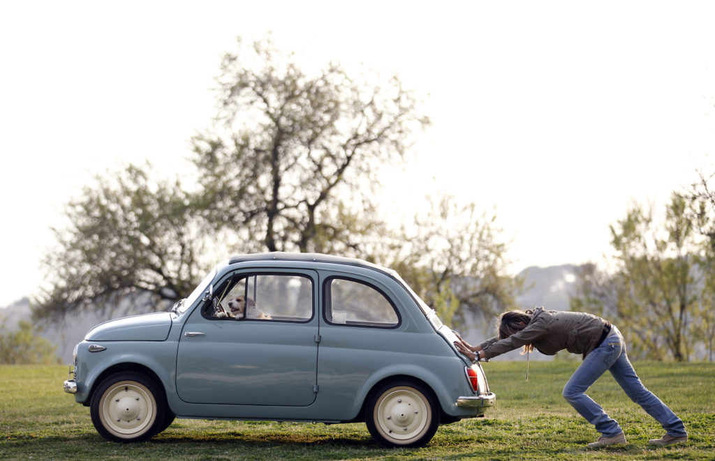 Im industriellen Zentrum Italiens läufts nicht mehr nach Wunsch: Eine Frau schiebt ihren Fiat 500 an. Foto: Alessandro Bianchi (Reuters)
