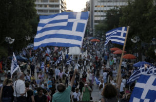 "Supporters of the No vote wave Greek flags after the referendum's exit polls at Syntagma square in Athens, Sunday, July 5, 2015. Greece faced an uncharted future as officials counted the results of a referendum Sunday on whether to accept creditors' demands for more austerity in exchange for rescue loans, with three opinion polls showing a tight race with a narrow victory likely for the ""no"" side. (AP Photo/Petros Giannakouris)"