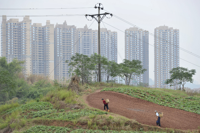 Farmers work at their vegetable field near newly finished residential buildings in Chongqing municipality, September 30, 2011. China's biggest municipality, Chongqing, has approached Hong Kong investors with the aim of selling distressed property assets and bolstering its finances, which are under a cloud after the fall of its ambitious leader, Bo Xilai, a source said. Bo was removed as Chongqing's Communist Party boss in March 2012. Picture taken September 30, 2011. REUTERS/Stringer (CHINA - Tags: POLITICS REAL ESTATE BUSINESS) CHINA OUT. NO COMMERCIAL OR EDITORIAL SALES IN CHINA - RTR31HV0