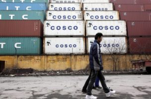 epa01594010 Men walk past stacks of shipping containers at a port facility in Shanghai, China on 09 January, 2009. China's trade surplus hit a record USD 40.1 billion in last November taking advantage of lower prices for raw materials that China imports, however most economists expect the monthly average in 2009 to drop to USD 20 billion as demand for Chinese exports remains weak; this along with China's increasing focus to invest domestically to prop the economy will likely mean significantly less money to buy American debt, at a time when America needs to issue large amounts to pay for it's own stimulus packages.  EPA/QILAI SHEN