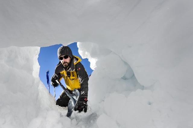 """Un conducteur de chiens, cherche une personne sous une avalanche lors d'un exercice """"Sauvetage d'urgence en cas d'avalanche"""" organise par le Secours Alpin Romand ce vendredi 27 novembre 2015 au Glacier 3000 au dessus des Diablerets. (KEYSTONE/Jean-Christophe Bott)"""