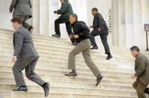 U.S. President Barack Obama (C) sprints up the steps of the Lincoln Memorial surrounded by Secret Service agents, to visit with tourists, a day after Congress came to agreement on funding the federal government, emphasizing that national parks, monuments and museums are kept open and filled with visitors, in Washington April 9, 2011.          REUTERS/Mike Theiler (UNITED STATES - Tags: POLITICS) - RTR2L18D