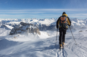Ein Skitourengaenger staret im Schneesturm zur Abfahrt vom Piz Tuf oberhalb Wergenstein im buendnerischen Schams, in der Bildmitte links die Felskanzel des Piz Tarantschun, am Samstag, 25. Januar 2014. (KEYSTONE/Arno Balzarini)