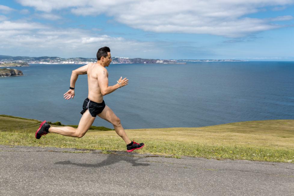 Shirtless man jogging at the coast