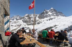 Alpinisten essen auf der Terrasse vor der Coazhuette der Sektion Raetia des Schweizerischen Alpenclubs, SAC, auf 2610 Meter ueber Meer im Berninagebiet oberhalb Pontresina im Oberengadin, am Donnerstag, 18. April 2013. (KEYSTONE/Arno Balzarini)