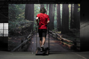 Young man on treadmill jogging in front photograph of forest