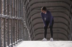 Sue Tran stretching before a snowy run in Salt Lake city, Utah.