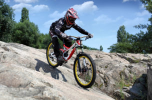 Sportsman in sportswear on a mountain bike rides on the stones in extreme style downhill
