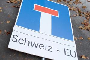 """Ein Sackgasse Strassenschild mit der Bezeichnung """"Schweiz - EU"""" liegt am Boden waehrend Aktivistinnen- und Aktivisten im Namen des Komitees """"Raus aus der Sackgasse"""" (RASA) 110 000 Unterschriften bei der Bundeskanzlei deponieren am Dienstag, 27. Oktober 2015, in Bern. (KEYSTONE/Lukas Lehmann)"""