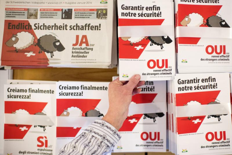 Eine Frau bedient sich an Werbematerial zur Durchsetzungsinitiative der SVP. Foto: Ennio Leanza (Keystone)