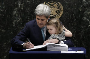 U.S. Secretary of State John Kerry holds his two-year-old granddaughter Isabelle Dobbs-Higginson as he signs the Paris Agreement on climate change at United Nations Headquarters in Manhattan, New York, U.S., April 22, 2016.    REUTERS/Mike Segar  - RTX2B8C9