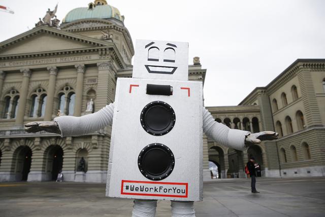"""Eine als Roboter verkleidete Person mit der Aufschrift """"We work for you"""" tanzt waehrend einer Aktion zum Start der Abstimmungskampagne für ein bedingungsloses Grundeinkommen, am Mittwoch, 27. Januar 2016 auf dem Bundesplatz in Bern. (KEYSTONE/Peter Klaunzer)"""
