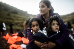 A mother hugs her children after they disembarked from a boat on the Greek island of Lesbos after crossing the Aegean Sea from Turkey on November 15, 2015. European leaders tried to focus on joint action with Africa to tackle the migration crisis, as Slovenia became the latest EU member to act on its own by barricading its border. AFP PHOTO/BULENT KILIC / AFP PHOTO / BULENT KILIC