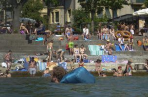 Leute sonnen sich am Rheinufer am Unteren Rheinweg in Basel am Samstag, 4. Juli 2015. (KEYSTONE/Georgios Kefalas)