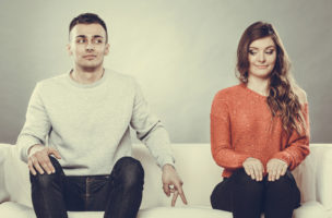 Shy woman and man. Guy sitting near attractive young woman on sofa and making hand gesture walking with finger to girl
