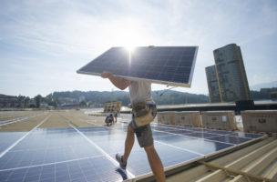 Montage einer Photovoltaikanlage auf dem Dach der Swissporarena in Luzern. Foto: Urs Flüeler (Keystone)